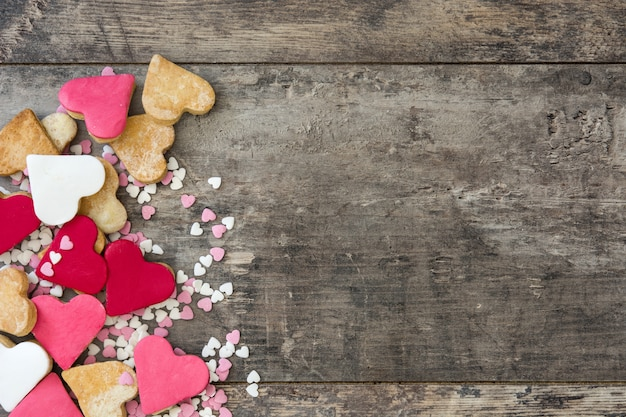 Biscotti del biglietto di s. valentino con forma del cuore sullo spazio della copia di vista superiore della superficie di legno