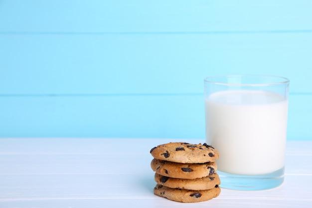 Biscotti del cioccolato e del bicchiere di latte su fondo blu