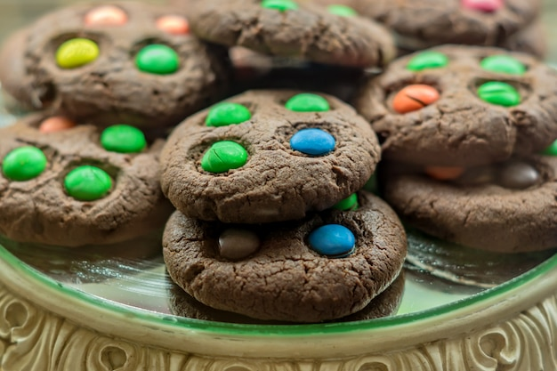 Biscotti del cioccolato zuccherato con le caramelle variopinte su un'esposizione, fuoco selettivo