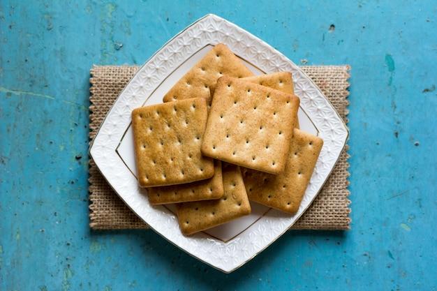 Biscotti del cracker in un primo piano blu del fondo onold del piattino ceramico bianco, vista superiore