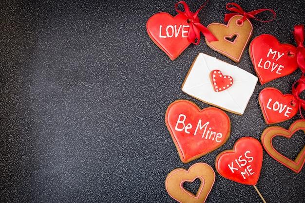 Biscotti del cuore con la lettera su fondo scuro