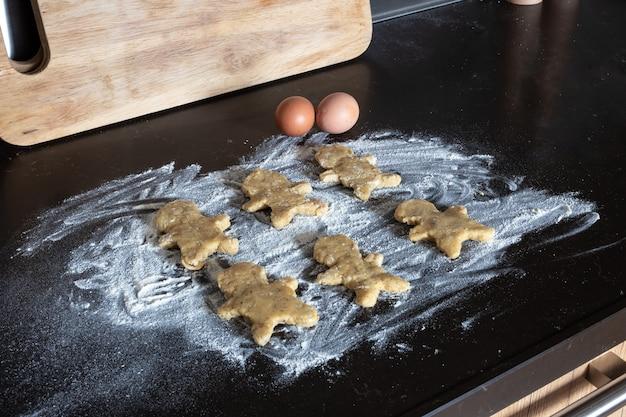 Biscotti dell'uomo di pan di zenzero di cottura della persona, mani della persona in pasta con il fiore in cucina accogliente