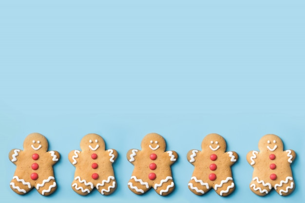 Biscotti dell'uomo di pan di zenzero di natale sulla tabella blu. vista dall'alto modello di cibo festivo. copyspace.