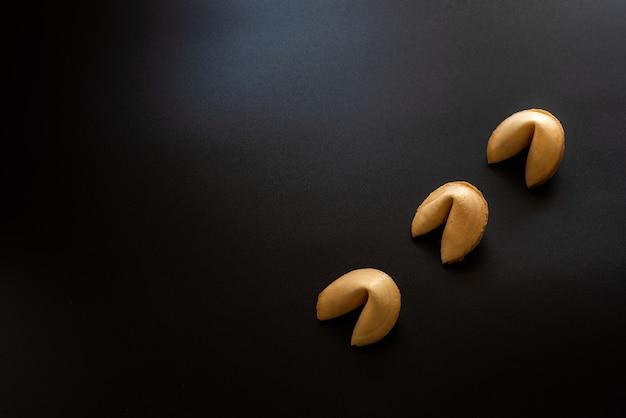 Biscotti della fortuna su sfondo nero.