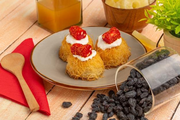 Biscotti della pasticceria orientale all'interno del piatto con ananas essiccato crema bianca e frutta secca sulla tavola di legno