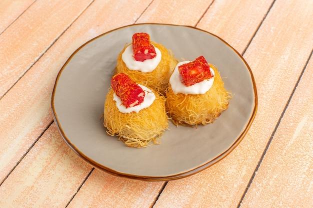 Biscotti della pasticceria orientale all'interno del piatto con crema bianca su legno