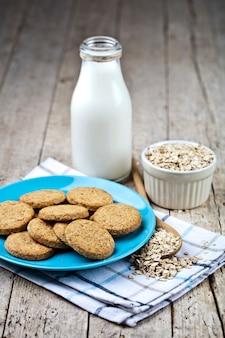 Biscotti di avena appena sfornati sul piatto in ceramica blu sul tovagliolo di lino, bottiglia di latte e scaglie di quercia
