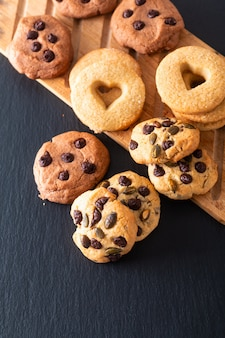 Biscotti di burro casalinghi dello zucchero di concetto dell'alimento sul bordo di legno sul piatto nero della pietra dell'ardesia con lo spazio della copia