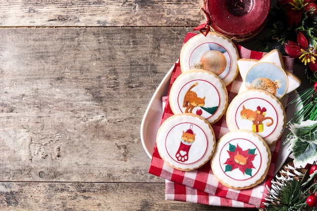 Biscotti di burro di natale decorati con i grafici di natale sulla tabella di legno, copyspace
