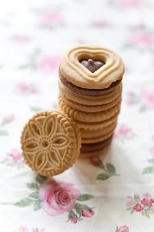 Biscotti di burro in piatto ceramico bianco e tovaglioli colorati sulla tavola di legno