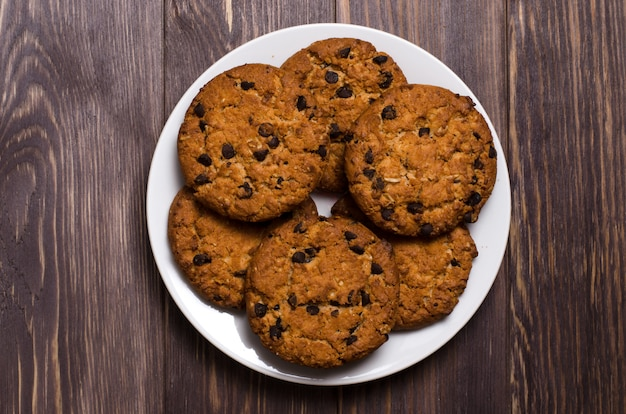 Biscotti di farina d'avena casalinghi su un piatto bianco. fondo in legno