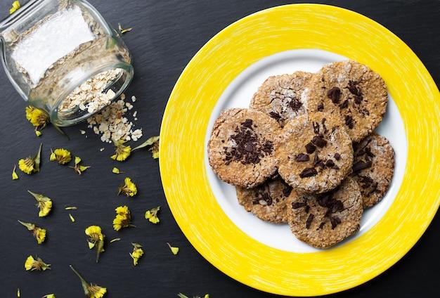 Biscotti di farina d'avena con cioccolato sul piatto giallo