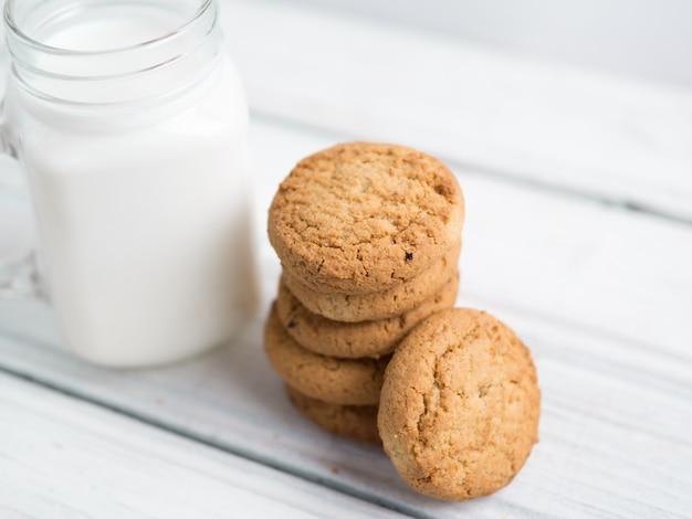 Biscotti di farina d'avena con latte su fondo di legno