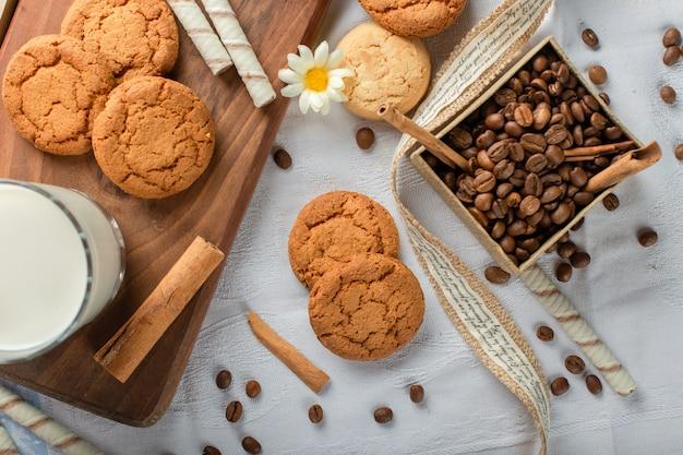 Biscotti di farina d'avena con un bicchiere di latte e scatola di chicchi di caffè.