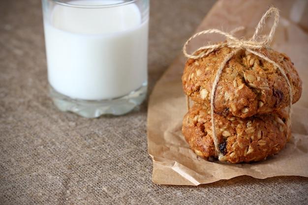 Biscotti di farina d'avena con uvetta legati con una corda con fiocco e un bicchiere di latte su carta kraft e tovaglia grigia ruvida