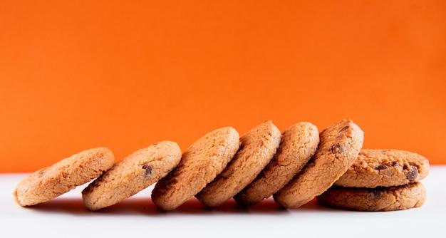 Biscotti di farina d'avena di vista superiore con cioccolato su un fondo bianco-arancio