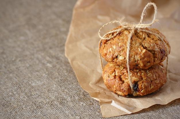 Biscotti di farina d'avena due con uvetta e riempitivi legati con una corda con un arco sulla tovaglia ruvida e grigia della carta da imballaggio del kraft.