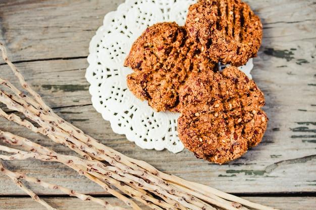 Biscotti di farina d'avena e mela in una ciotola con semi di sesamo e data, fotografati con luce naturale.