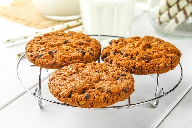Biscotti di farina d'avena fatti in casa biscotti su una griglia di ferro su un tavolo di legno bianco.