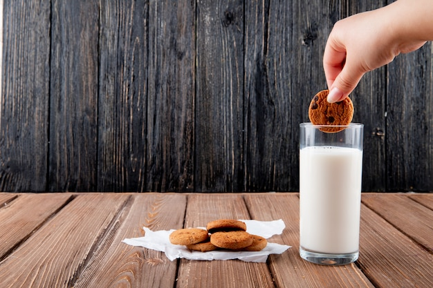 Biscotti di farina d'avena inzuppati della donna di vista frontale su carta da lucido con bicchiere di latte su un fondo di legno