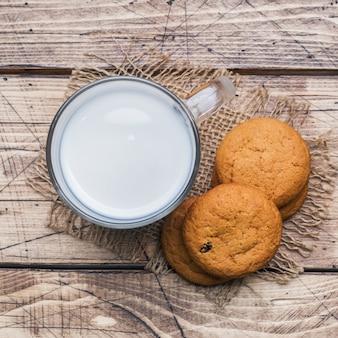 Biscotti di farina d'avena naturali e un bicchiere di latte su un di legno. stile rustico.
