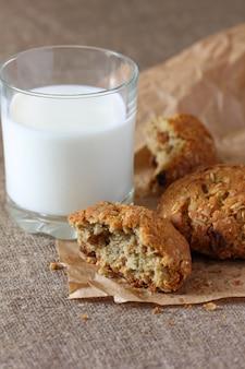 Biscotti di farina d'avena rotti con gatti e vetro con latte su carta kraft e tovaglia di tela da imballaggio.