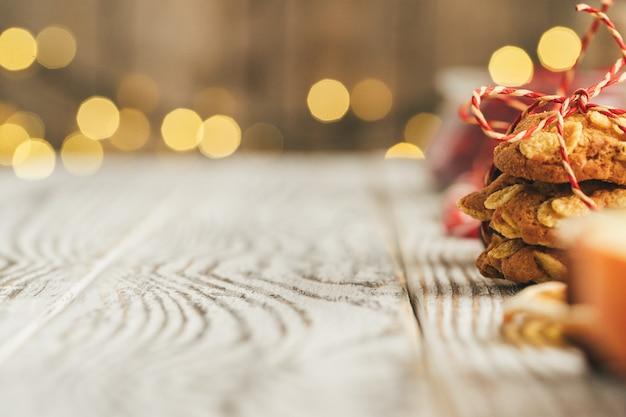 Biscotti di farina d'avena su un vecchio fondo di legno con bastoncini di cannella e decorazioni