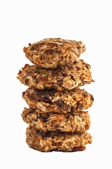 Biscotti di farina d'avena vegani con le date e una banana isolata su fondo bianco.