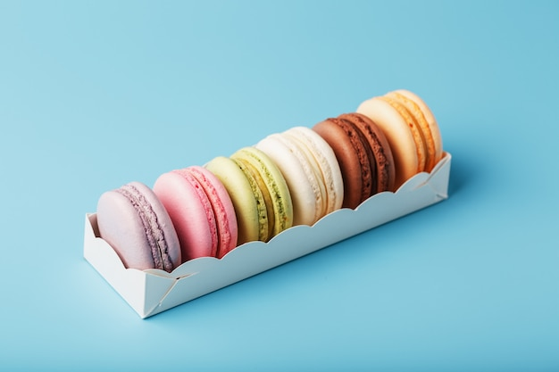 Biscotti di maccheroni di diversi colori in una scatola bianca su sfondo blu.