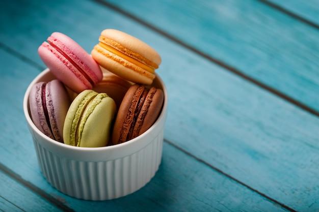 Biscotti di maccheroni francesi multicolori in un piatto bianco ,. spazio libero, vista dall'alto.