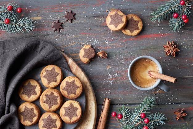 Biscotti di natale con motivo a stelle al cioccolato con caffè espresso, cannella e ramoscelli di abete decorati