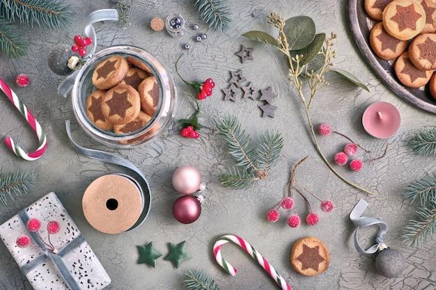 Biscotti di natale con motivo a stelle di cioccolato con varie decorazioni di natale e bastoncini di zucchero