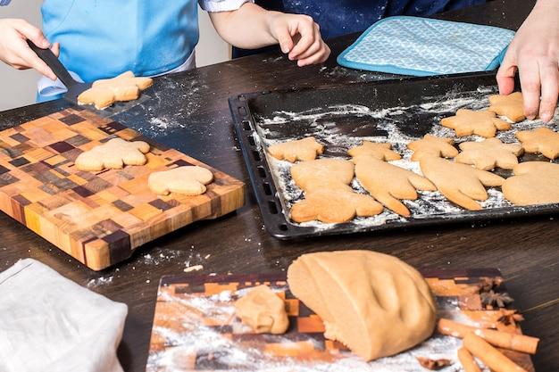 Biscotti di natale gingerbread e mani dei bambini.