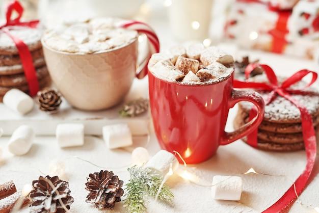 Biscotti di natale, latte, cacao, marshmallow, caramelle su un piatto bianco vicino alla finestra