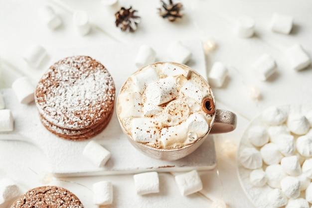 Biscotti di natale, latte, cacao, marshmallow, piatto di meringa vicino alla finestra