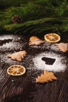 Biscotti di pan di zenzero a forma di cuore e abete di natale, zucchero a velo sul tavolo di legno, frutta secca di agrumi, ramo di abete, vista di angolo, fuoco selettivo