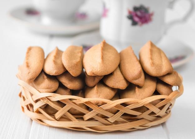 Biscotti di pan di zenzero con una tazza di caffè su una tavola di legno bianca.
