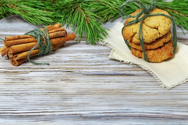Biscotti di panpepato e bastoncini di cannella con ramoscelli di abete.