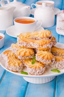 Biscotti di pasta frolla con caramello e la noce di cocco su un piatto sulla tavola di legno