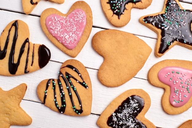 Biscotti di pasta frolla fatti in casa, biscotti ricci con glassa rosa e cioccolato. biscotti decorativi su un bianco