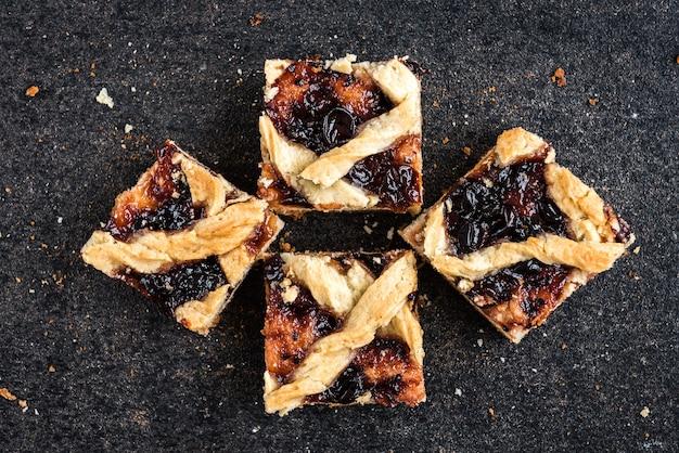 Biscotti di pasta frolla fatti in casa con marmellata sul nero.