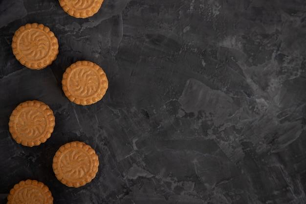 Biscotti di pasta frolla rotondi con uno strato di crema su oscurità
