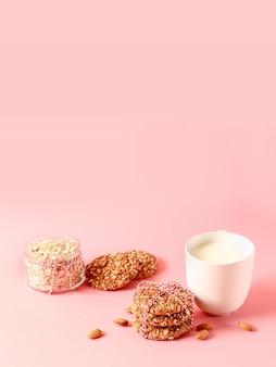 Biscotti di pepita di avena, noci, tazza di latte su uno sfondo rosa.