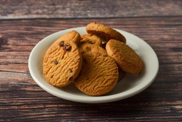 Biscotti di pepita di cioccolato e dell'avena sul fondo di legno rustico della tavola