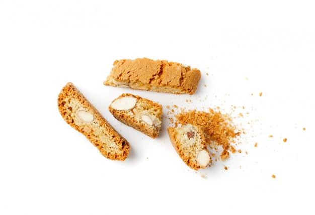 Biscotti di prato sbriciolati isolati su sfondo bianco. biscotti italiani tradizionali dei dadi di cantuccini con le briciole. cantucci frollini fatti in casa con vista dall'alto di mandorle