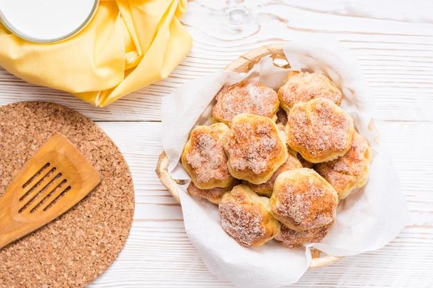 Biscotti di ricotta cosparsi di zucchero in un cestino e una tazza di latte su un tavolo di legno. copyspace