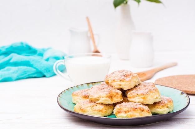 Biscotti di ricotta cosparsi di zucchero su un piatto e una tazza di latte su un tavolo di legno