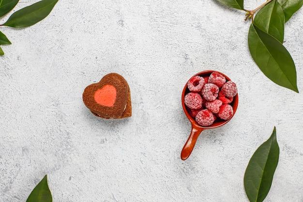 Biscotti di san valentino a forma di cuore con lamponi congelati su sfondo chiaro