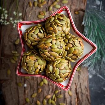 Biscotti di vista superiore con i semi di zucca con nel piatto a forma di stella su superficie di legno