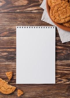 Biscotti di vista superiore e blocco note vuoto dello spazio della copia
